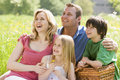 Family sitting outdoors with picnic basket smiling Stock Photos
