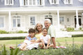 Family Sitting Outside House On Lawn Royalty Free Stock Photo