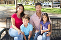 Family Sitting On Park Bench Together Royalty Free Stock Photo