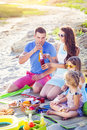 Family sitting on the sand at the beach at the summer picnic Royalty Free Stock Photo