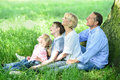 Family sitting in shade under the tree of four and looking up Stock Photography