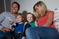 Family sitting on sofa watching tv together at home with son using remote control Stock Photo