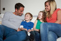 Family sitting on sofa watching tv together whilst looking at each other smiling Stock Photo