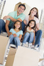 Family sitting on staircase with boxes in new home Stock Photo