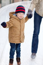 Family skating happy smiling little boy ice and holding his parent Royalty Free Stock Photography