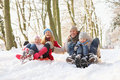 Family Sledging Through Snowy Woodland Royalty Free Stock Photography