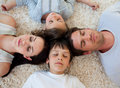 Family sleeping on the floor with heads together Stock Images
