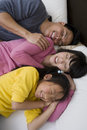 Family Sleeping Together In Bed Royalty Free Stock Photos