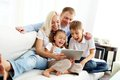 Family on sofa portrait of ecstatic with two children looking at something funny in touchpad Royalty Free Stock Photography