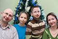 Family standing near Christmas tree Stock Photo