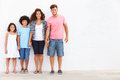 Family standing outdoors against white wall� Stock Image