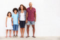 Family standing outdoors against white wall� Royalty Free Stock Images