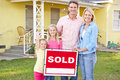 Family Standing By Sold Sign Outside Home Royalty Free Stock Image