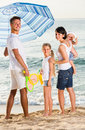 Family standing under sun umbrella