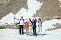 The family is staying on snow in mountains from five persons against rock slope Stock Photo