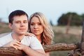 Family at sunset young couple near a wooden fence Royalty Free Stock Image