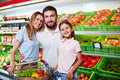 Family in supermarket of three looking at camera Royalty Free Stock Photography