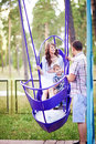 Family swinging together in the summer park Royalty Free Stock Photo