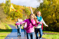 Family take walk in autumn forest flying kite Stock Images