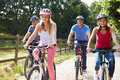 Family with teenage children on cycle ride in countryside daylight having fun Stock Image