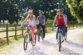 Family with teenage children on cycle ride in countryside wearing helmets Stock Photo