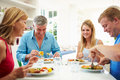 Family with teenage children eating meal at home together having a conversation Royalty Free Stock Photos