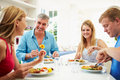 Family with teenage children eating meal at home together sitting around table Royalty Free Stock Photography