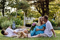 Family of three in front of flower garden and their yellow lab having fun Stock Image