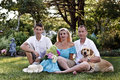 Family of three in front of flower garden and their yellow lab having fun Stock Photography