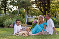 Family of three by garden together and yellow lab joining them Royalty Free Stock Images