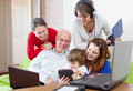 Family of three generations uses few various electronic device devices in home interior Stock Photo