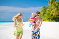 Family of three having tropical vacation on maldives walking the white sandy beach Stock Photos