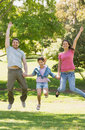Family of three holding hands and jumping at park Stock Photography
