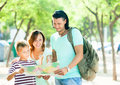 Family of three searching way at paper map happy in park Royalty Free Stock Photo