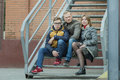 Family of three street urban portrait sitting on metal stairs at brick building background Royalty Free Stock Photo
