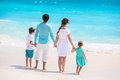 Family on a tropical beach vacation back view of caucasian at Royalty Free Stock Photo