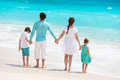 Family on a tropical beach vacation back view of caucasian at Stock Photos
