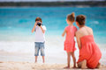 Family on tropical vacation boy photographing his mother and little sister at beach Royalty Free Stock Photography