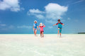 Family at tropical vacation mother and kids on a caribbean running shallow water Royalty Free Stock Image