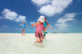 Family at tropical vacation mother and kids on a caribbean running shallow water Royalty Free Stock Photo