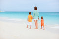Family on tropical vacation walking along the beach Royalty Free Stock Images
