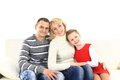 Family with two children sitting on white leather sofa Royalty Free Stock Image