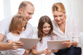 Family and two kids with tablet pc computers children technology money home concept smiling little girls at home Royalty Free Stock Photos