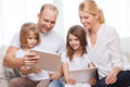 Family and two kids with tablet pc computers children technology money home concept smiling little girls at home Royalty Free Stock Image