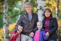 Family with two mature parents and son with daughter standing in park at autumn stand Stock Images