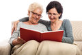 Family of two women sharing memories photo album happy senior and adult at home looking at laughing sitting on sofa with blanket Stock Photos