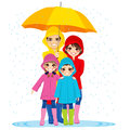 Family under umbrella happy with raincoats big on rainy day Stock Photo