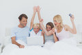 Family using a laptop in bed and raising their arms to show their success Royalty Free Stock Photos