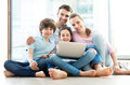 Family using laptop at home smiling relaxing Stock Image