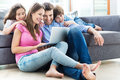 Family using laptop at home smiling relaxing Stock Photography
